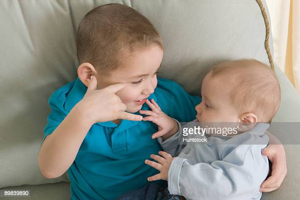 Boy signing the phrase 'I Love You ' in American sign language while communicating with his brother
