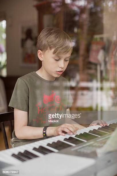 Boy signing while playing piano in house