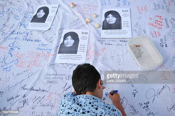 A boy signs a petition calling for an end to stoning during a demonstration by members of the International Committee Against Stoning in Trafalgar...