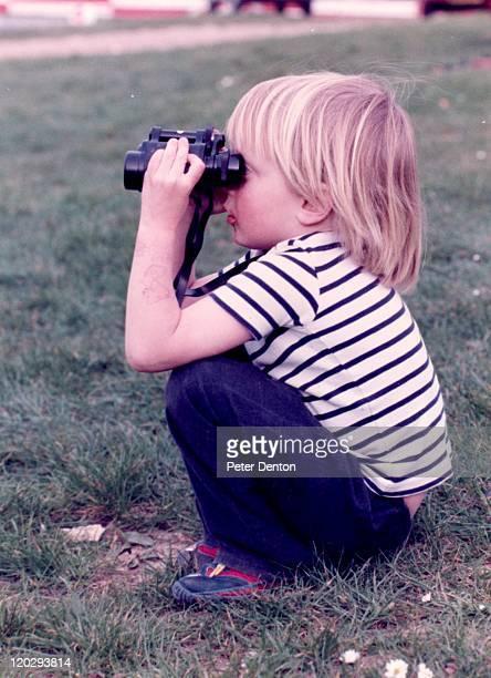 Boy siiting on heel and looking from binocular