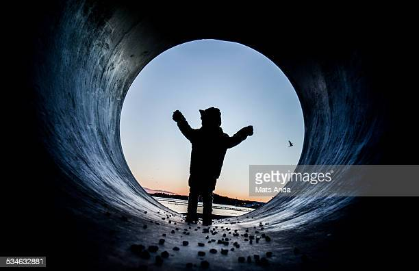 Boy silhouetted in big pipe tube