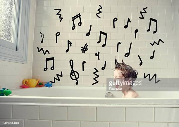Boy singing in the bath with music symbols