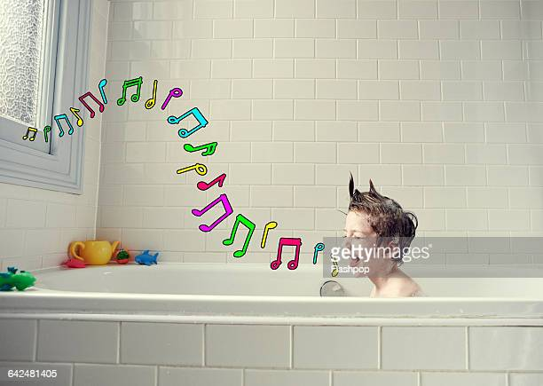 Boy singing in the bath with musical symbols