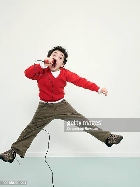 Boy (7-9) singing into microphone and jumping, portrait