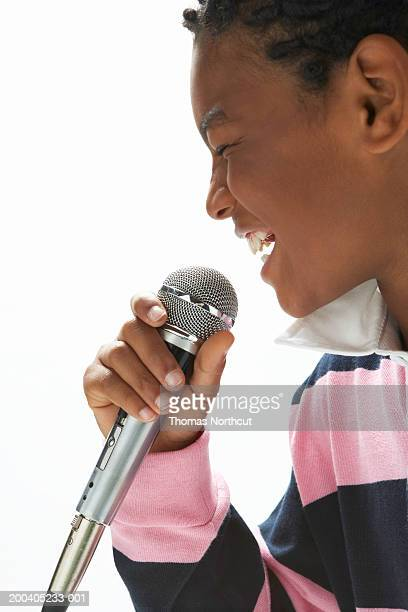 Boy (9-11) singing into microphone, eyes closed, side view