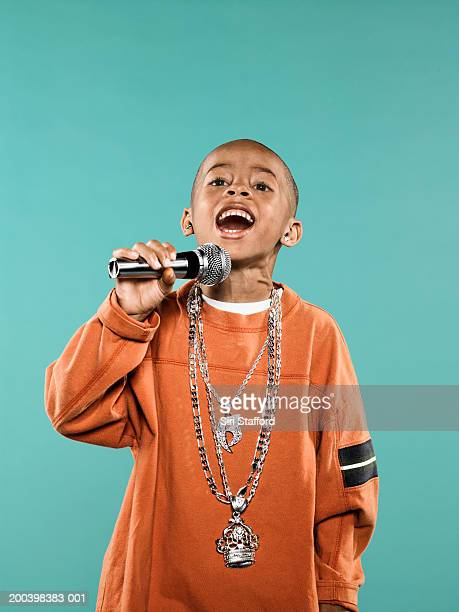 Boy (4-6) singing on microphone