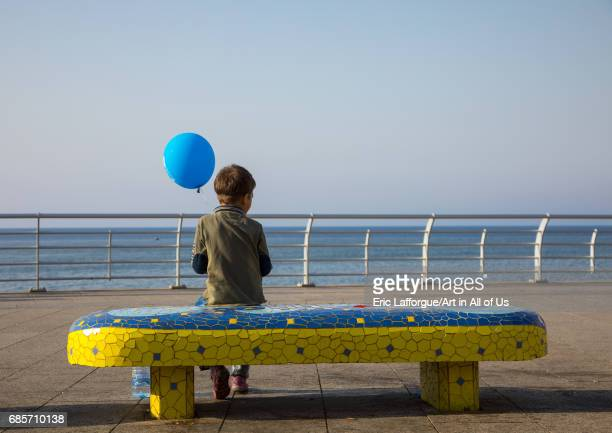 Boy sit on a bench with a balloon in the corniche Beirut Governorate Beirut Lebanon on April 28 2017 in Beirut Lebanon