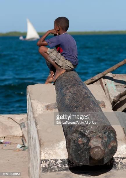 Boy sit on a cannon along a dockside, Lamu County, Lamu, Kenya on March 1, 2011 in Lamu, Kenya.