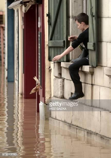 A boy sit on the window sill above flood waters following heavy rains in SaliesdeBearn south western France on June 13 2018