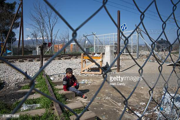 A boy sits alone in front of the border gate at the Idomeni refugee camp on the Greek Macedonia border on March 20 2016 in Idomeni Greece Thousands...