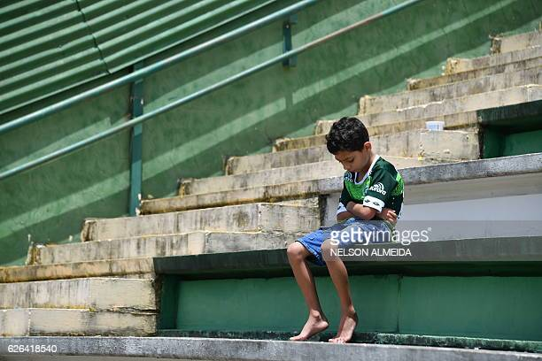 TOPSHOT A boy sits alone on the stands during a tribute to the players of Brazilian team Chapecoense Real who were killed in a plane accident in the...