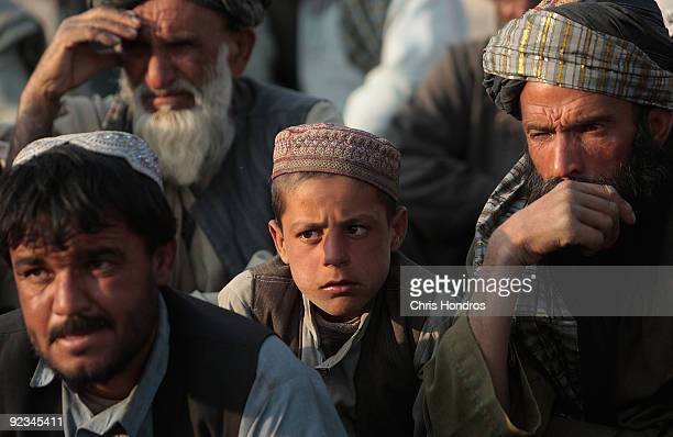 A boy sits among Afghan Pashtun tribal elders during a traditional meeting to discuss American and Canadian military actions on their lands October...