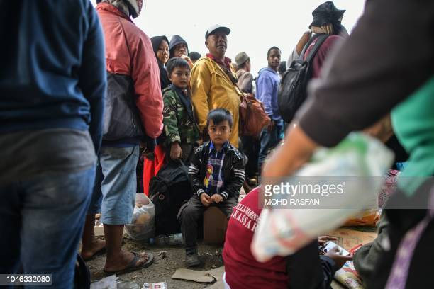 TOPSHOT A boy sits as others queue behind a line before boarding military airplanes for evacuations at the Mutiara SIS AlJufrie Airport in Palu...