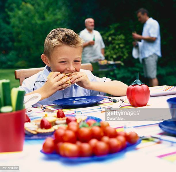 Boy Sits at a Table Eating While His Father and Grandfather Stand at a Barbeque