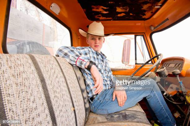 boy sits behind steering wheel in truck on ranch - アメリカ文化 ストックフォトと画像