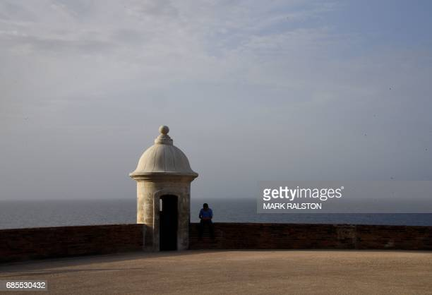 A boy sits beside an old Spanish watchtower at the El Morro Fortress on May 15 2017 in San Juan Puerto Rico as the former Spanish colony of 35...