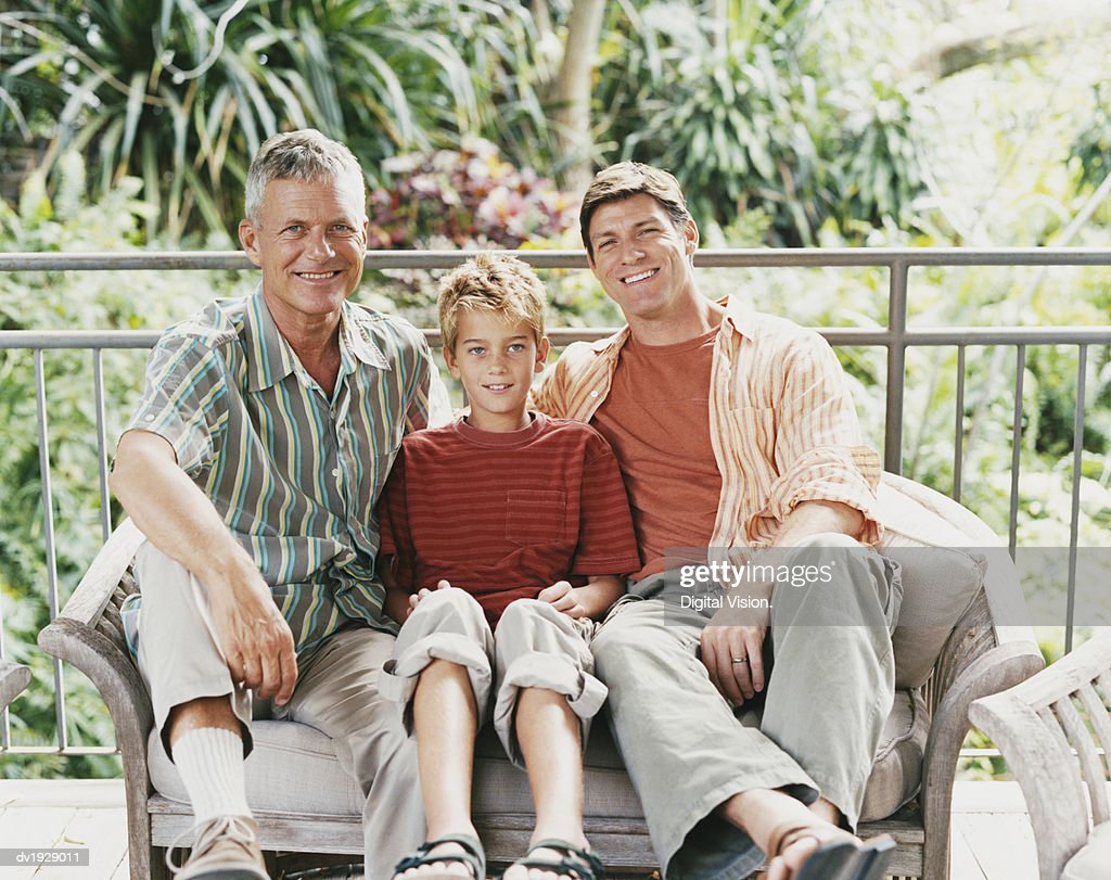 Boy Sits Between His Father and Grandfather on a Bench : Stock Photo