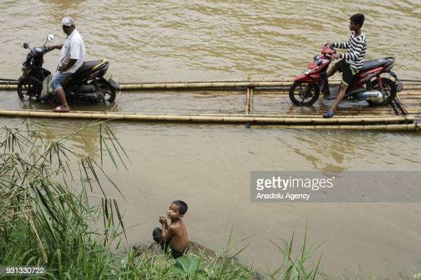 A boy sits by the river bank as several people assist motorcyclists to pull up their vehicles onto wooden raft to cross Cisadane River in Rumpin...