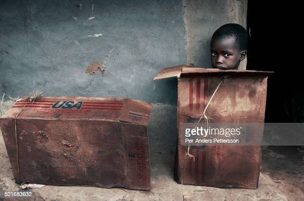 A boy sits in a cardboard box outside a hut in Umyama a camp for displayed people in nortern Uganda About 15 million people have fled villages and...