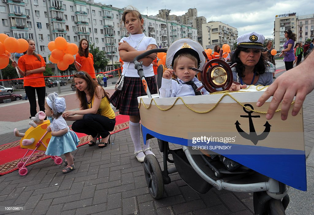 A boy sits in a pram made like a ship du