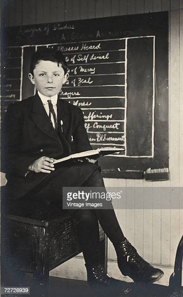 A boy sits in a suit and knickerbockers with his legs crossed and a writing tablet in his lap next to a blackboard on which is written information...