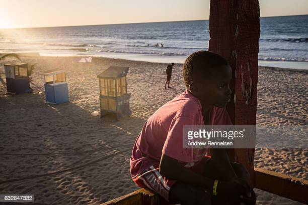 Boy sits in from a watch tower overlooking an almost empty beach on January 24, 2017 in Serekunda, The Gambia. Many popular travel destinations still...