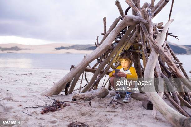 Boy sits in homemade driftwood teepee on beach with device/phone
