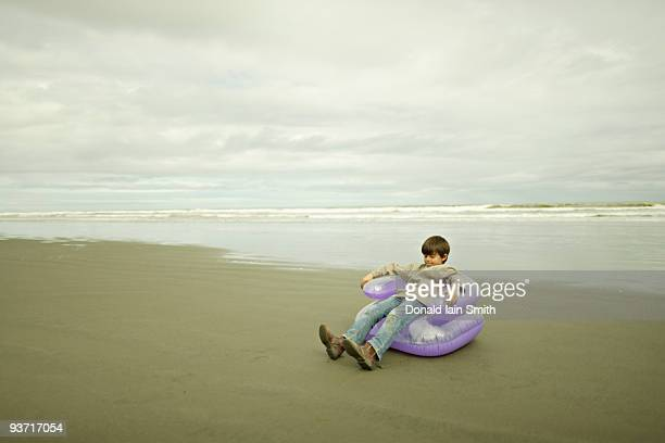 Boy sits in inflatable chair at the beach