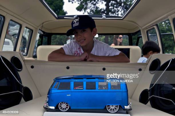 A boy sits inside a Kombi during an exhibition at the Volkswagen plant in Sao Bernardo do Campo southern Sao Paulo Brazil on December 8 2013 VW's...