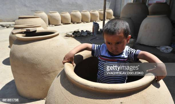 Boy sits inside of a round furnace of clay in the town of Osh some 500 km from the Kyrgyz capital Bishkek on May 11, 2017. The clay is used to make...