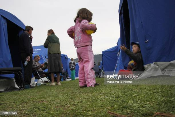 Boy sits near a tent in a temporary shelter camp for displaced people after an earthquake hit the region on April 8, 2009 in L' Aquila, Italy. The...
