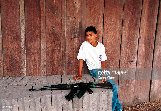 A boy sits near an AK47 assault rifle at a FARC check point February 26 2001 in Cristales Colombia The FARC is the country's largest rebel group and...