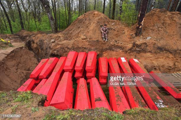 A boy sits next to a mass grave with coffins with the remains of Red Army soldiers killed in World War Two during a reburial ceremony at the...