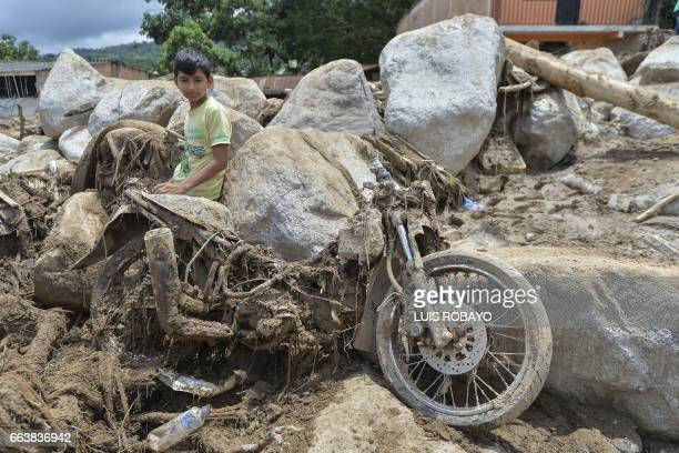 TOPSHOT A boy sits next to a motorcycle destroyed by the mudslides in Mocoa Putumayo department southern Colombia on April 2 2017 The death toll from...