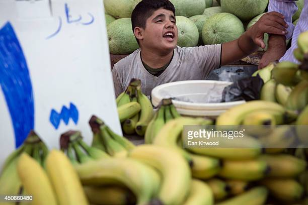 A boy sits on a stall selling bananas in the market on June 15 2014 in Erbil Iraq In Iraq's capital city of Baghdad and other towns and cities...