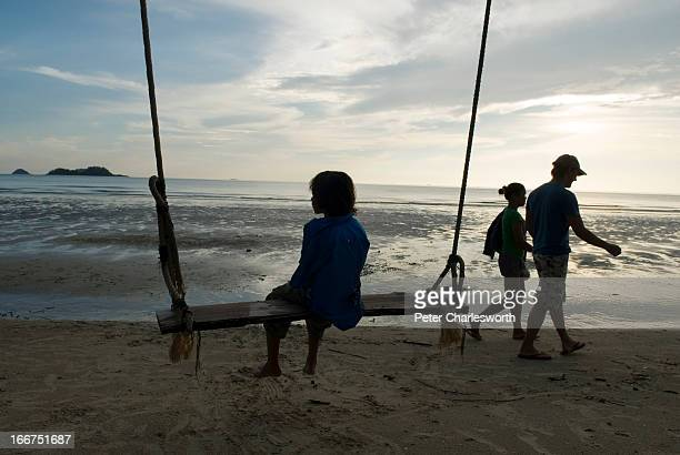 A boy sits on a swing on a desolate tropical beach on the west coast of Koh Chang island PARTIAL MODEL RELEASED