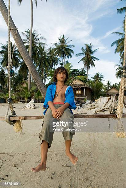 A boy sits on a swing on a desolate tropical beach on the west coast of Koh Chang island MODEL RELEASED