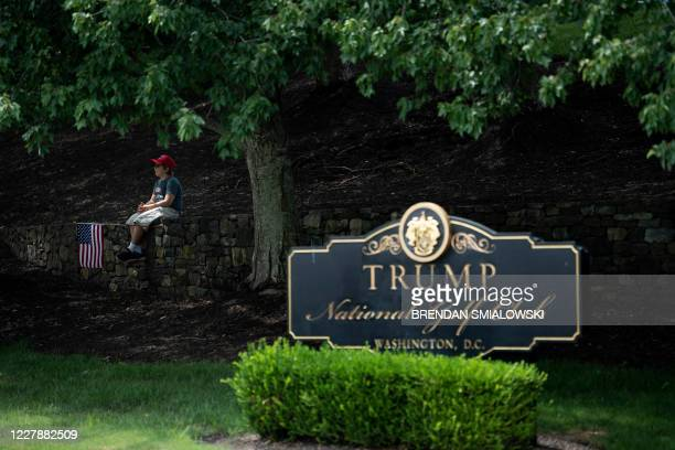 Boy sits on a wall as protesters and supporters of US President Donald Trump gather outside the Trump National Golf Club as the president golfs at...