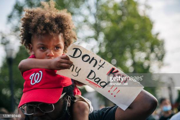Boy sits on his fathers shoulders while holding a sign on August 24, 2020 in Kenosha, Wisconsin. A night of civil unrest occurred after the shooting...