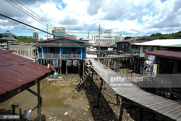A boy sits on the edge of a wooden walkway at Kampung Air on November 7 2013 in Bandar Seri Begawan Brunei Darussalam Sultan Hassanal Bolkiah has...