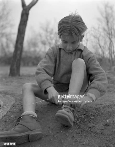 A boy sits on the ground outside in order to lace up his shoes Trieste Italy 1950