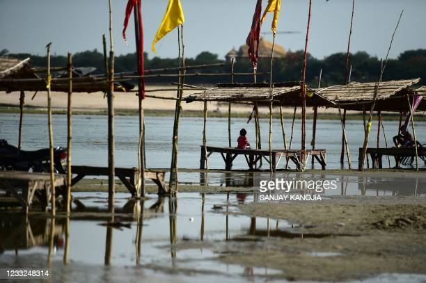 Boy sits under the shade of a partially submerged hut on the banks of river Ganges as its water level rises in Allahabad on June 3, 2021.