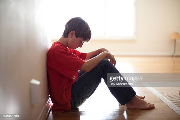 boy sitting against wall - one teenage boy only stock pictures, royalty-free photos & images