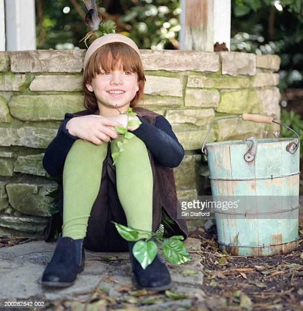 Boy (6-8) sitting against wishing well