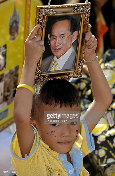 A boy sitting among wellwishers holds a portrait of Thailand's revered King Bhumibol Adulyadej in Bangkok 05 December 2007 during the monarch's 80th...