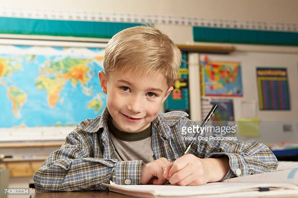 Boy (8-9) sitting and writing at desk in classroom, smiling, portrait