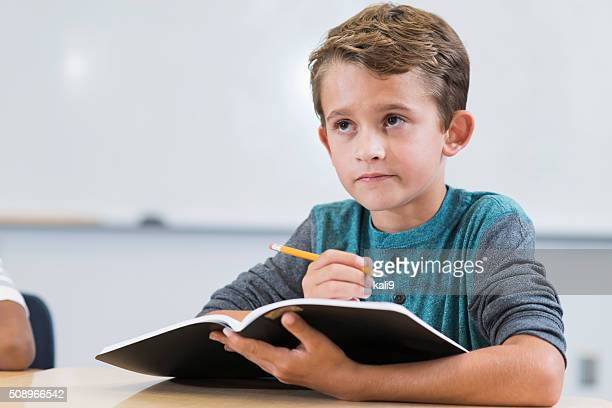 Boy sitting at desk in class holding notebook and pencil