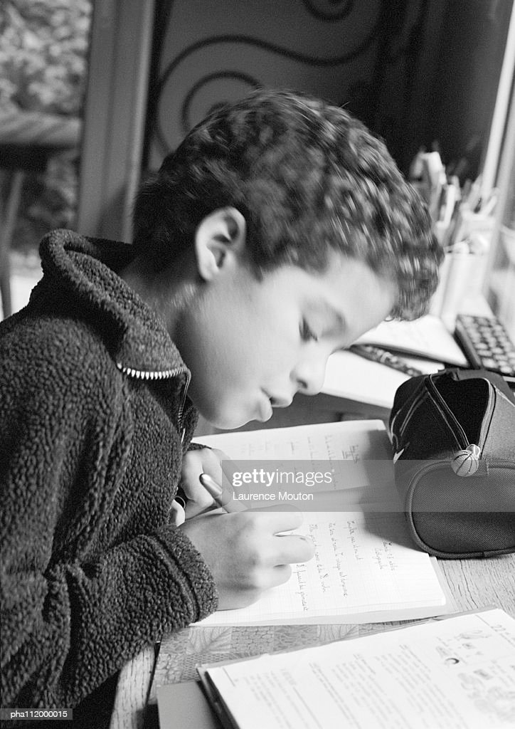 Boy sitting at desk, writing in notebook, side view, b&w : Stockfoto