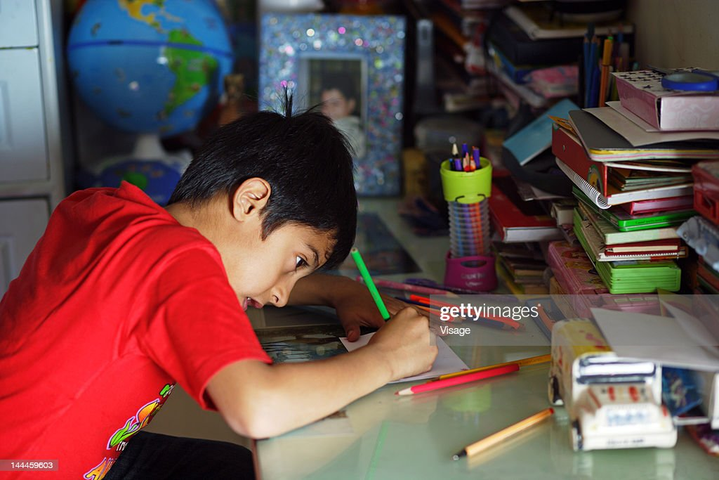 Boy sitting at desk, writing with pencil : Stock Photo