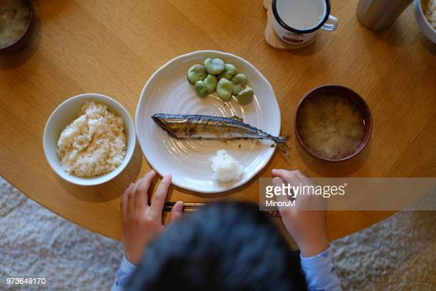 boy sitting at dining table ready to eat dinner - fish love ストックフォトと画像